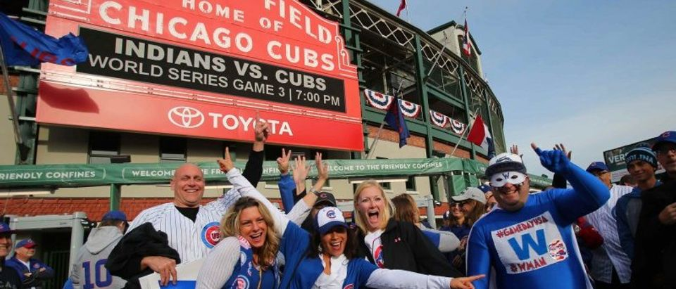 Chicago Cubs fans pose in front of Wrigley Field before game three of the 2016 World Series between the Chicago Cubs and the Cleveland Indians, in Chicago