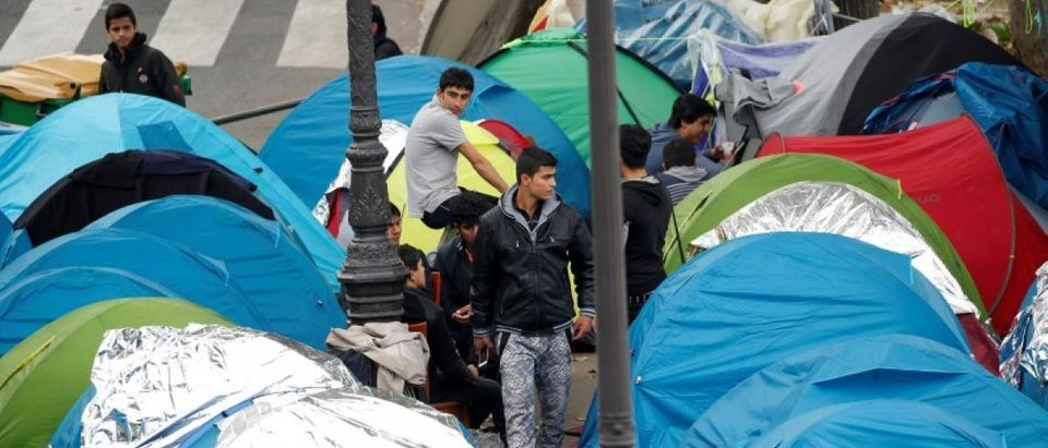 Migrants stand near their tents at a makeshift migrant camp on a street near the metro stations of Jaures and Stalingrad in Paris, France, October 28, 2016. REUTERS/Charles Platiau