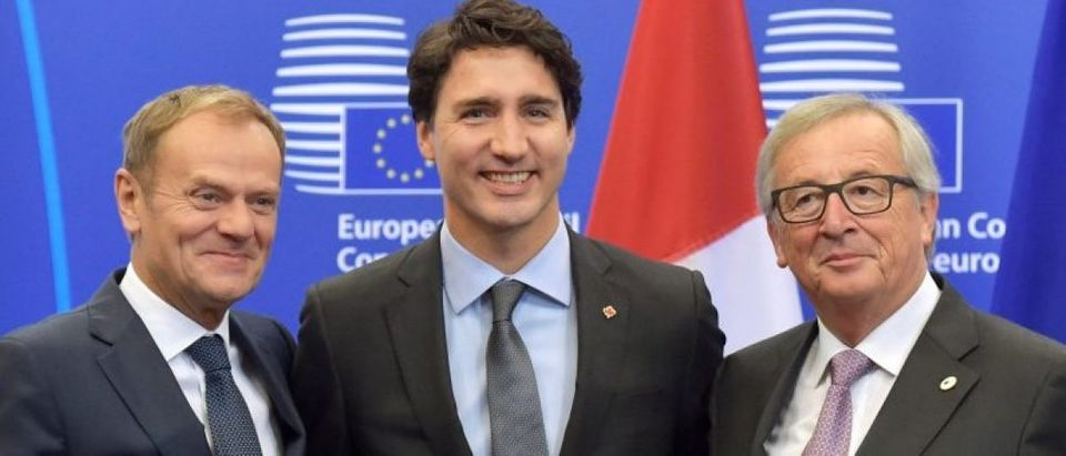 Canada's PM Trudeau poses with EU Council President Tusk and EC President Juncker before signing the CETA at the European Council in Brussels