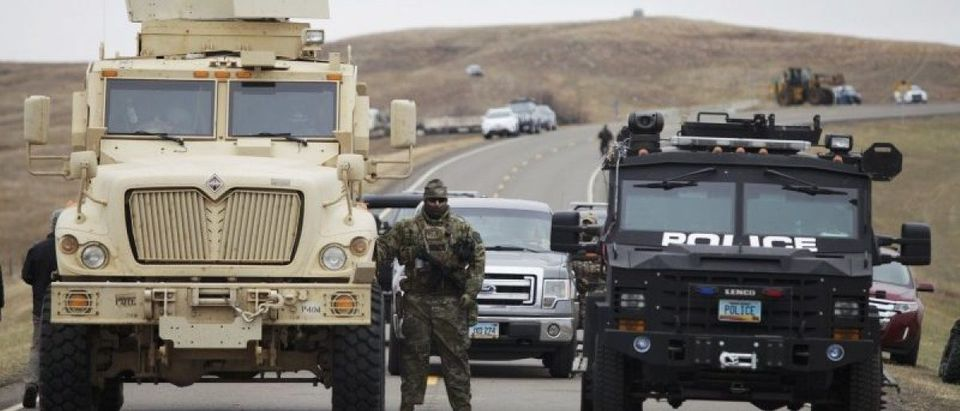 A North Dakota law enforcement officers stands next to two armored vehicles just beyond the police barricade on Highway 1806 near a Dakota Access Pipeline construction site near the town of Cannon Ball.