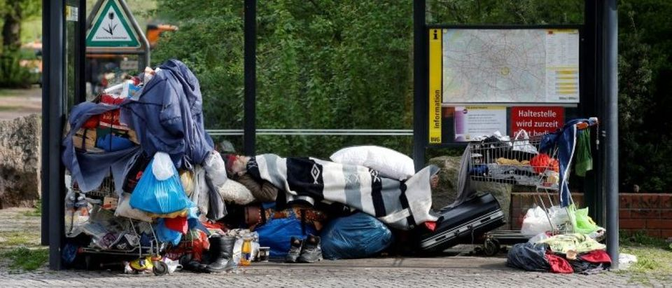 Homeless man sleeps inside a bus stop at Berlin's district of Kreuzberg