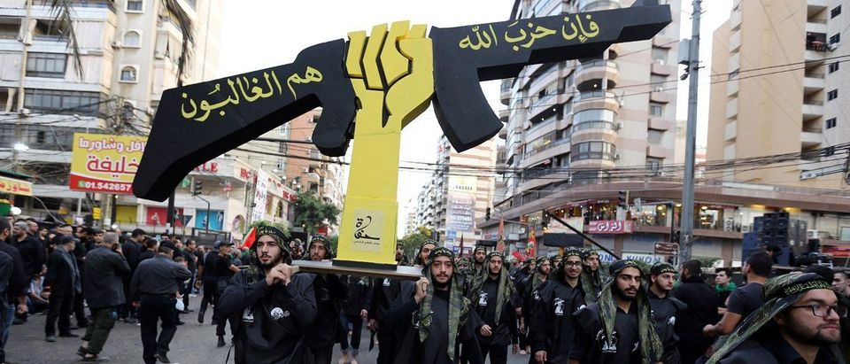 Lebanese Hezbollah supporters carry a replica of Hezbollah emblem during a religious procession to mark Ashura in Beirut's southern suburbs