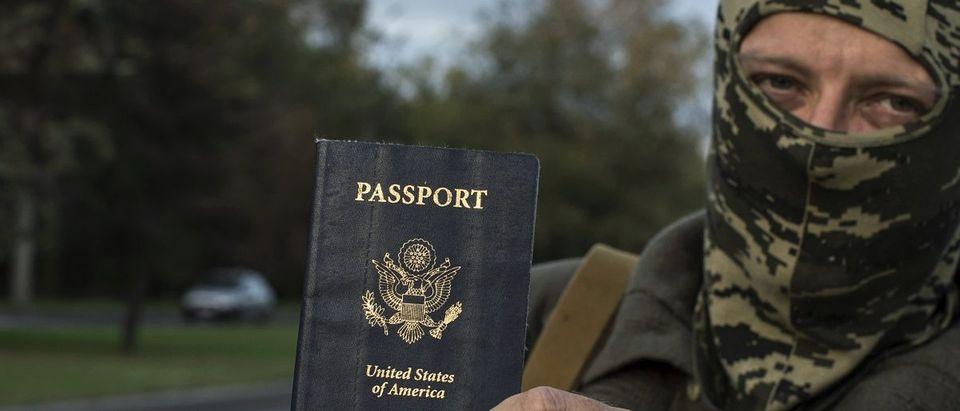 "An American who calls himself ""Hunter"" holds his passport in Donetsk, eastern Ukraine"