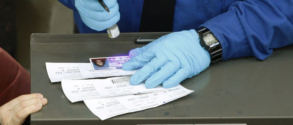 An employee of the U.S. Transportation Security Administration checks the authenticity of a passenger's driver's license as he matches names on boarding passes at Washington Reagan National Airport
