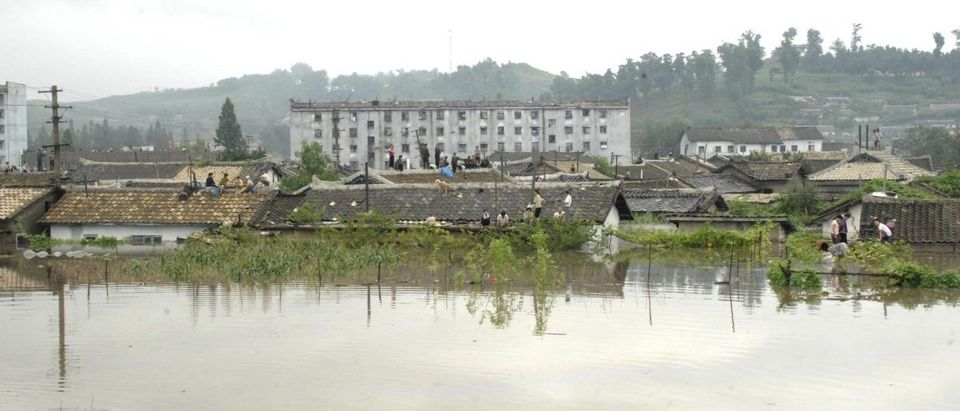 North Koreans are seen on top of houses at a flooded village in Anju