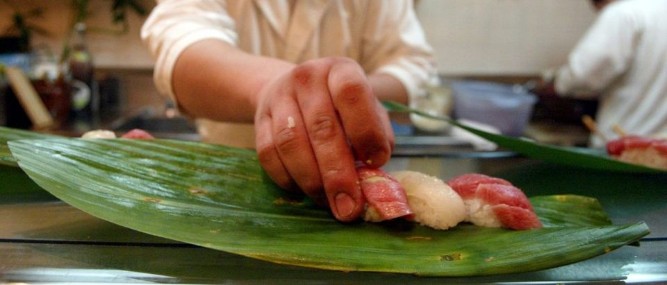 A JAPANESE COOK PREPARES A SUSHI DISH IN A RESTAURANT IN TOKYO.