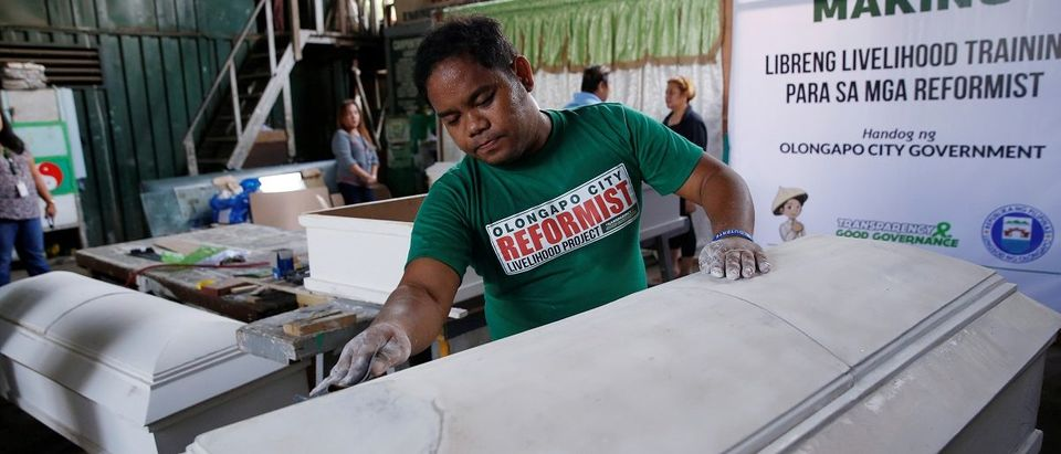 A former drug user undergoing rehabilitation makes coffins as part of a local government drug rehabilitation program in Olongapo city