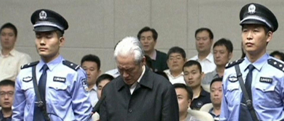 Still image of Zhou Yongkang, China's former domestic security chief, standing between his police escorts as he listens to his sentence in a court in Tianjin