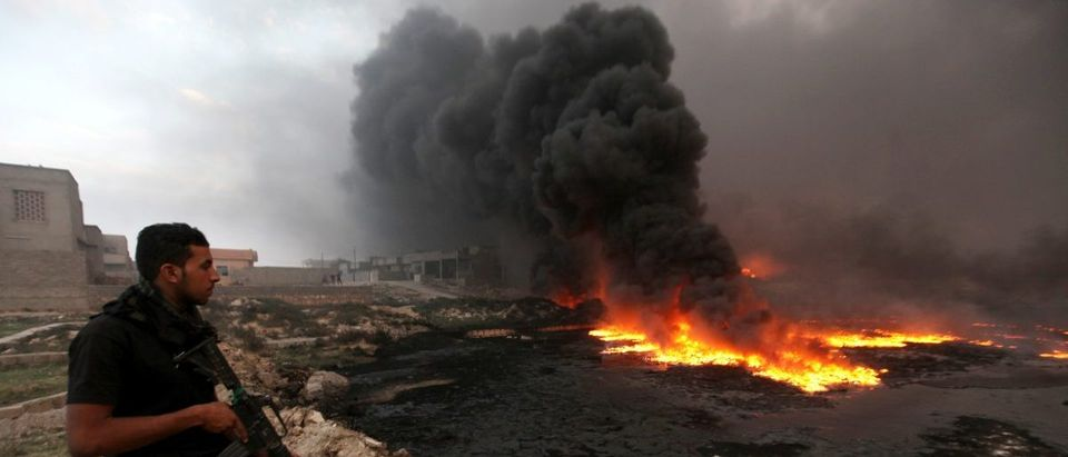 A member of Iraqi security forces stands with weapon, near oil wells set ablaze by Islamic State militants before fleeing oil-producing region of Qayyara