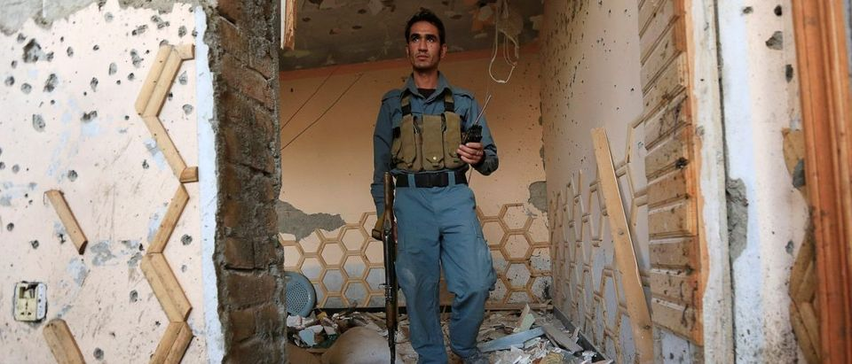 An Afghan police inspects a house after a suicide attack at an elders meeting gathering on the outskirts of Jalalabad city