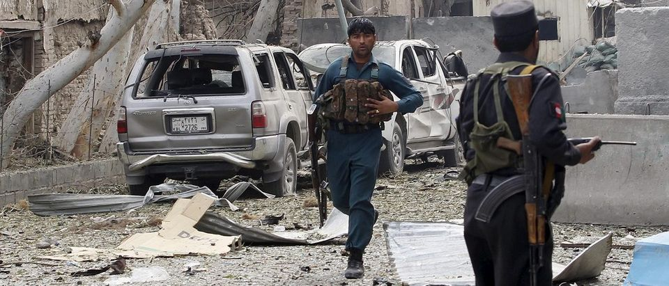An Afghan policeman runs during the gunfire in front of the Indian consulate in Jalalabad