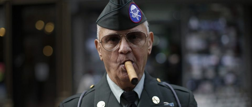 Vietnam War veteran Vincent Bochicchio from New York City smokes a cigar as he stands in uniform to watch the Veterans Day parade on 5th Avenue in New York