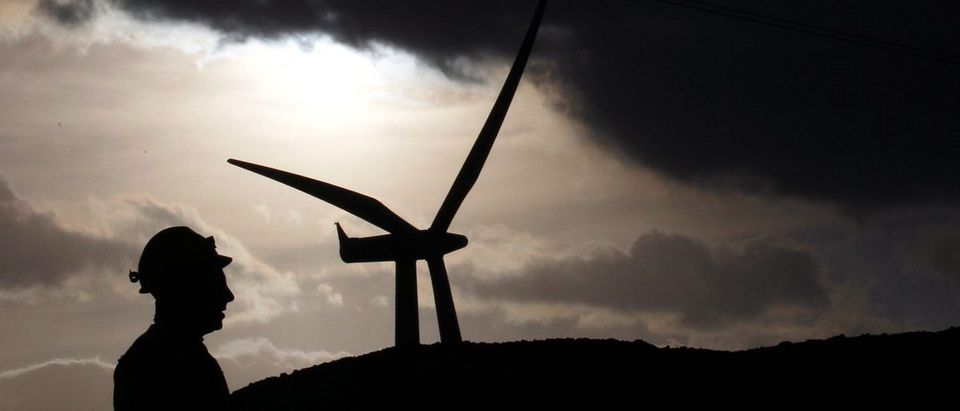 An Alcoa Inc. aluminium worker is silhouetted next to Aeolian Power's wind turbine in Sardinian, in Portovesme