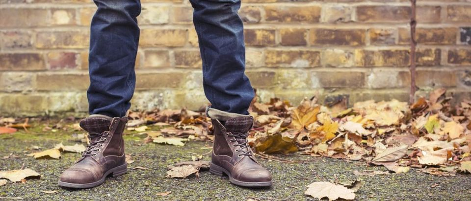 A man wears high ankle boots during autumn (Photo via Shutterstock)