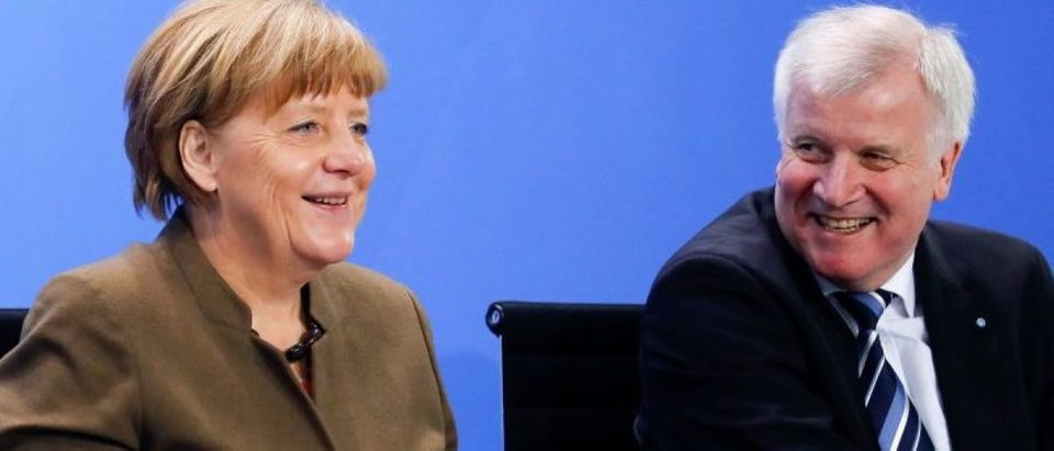 German Chancellor Merkel smiles next Bavarian state premier and leader of the Christian Social Union Seehofer during a news conference at the Chancellery in Berlin