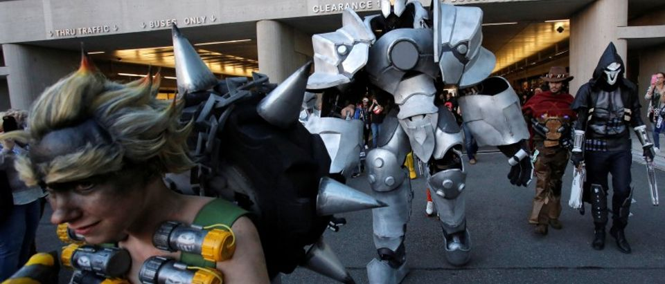 A man in a dressed as Reinhardt from Overwatch walks with other attendees at New York Comic Con in Manhattan