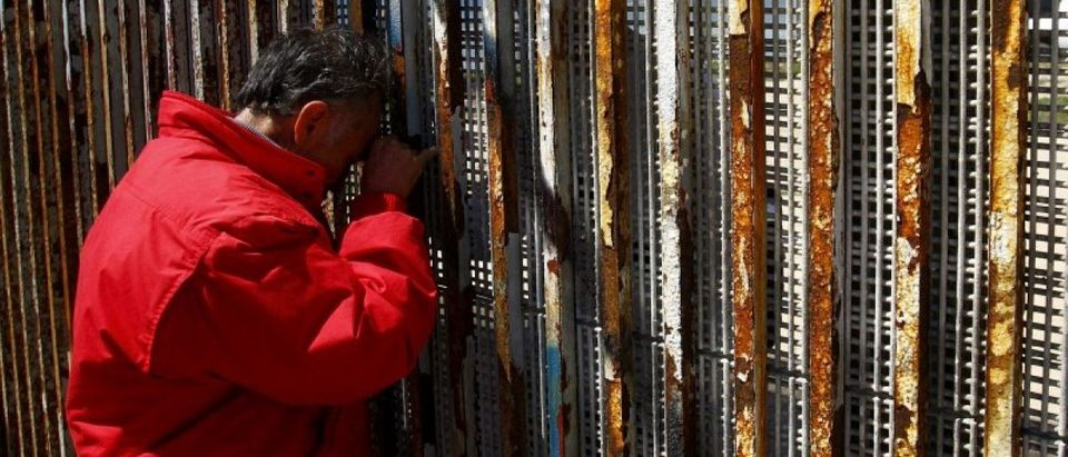 Man talks to relatives at a wall separating Mexico and the United States, as photographed from Playas Tijuana, in Tijuana