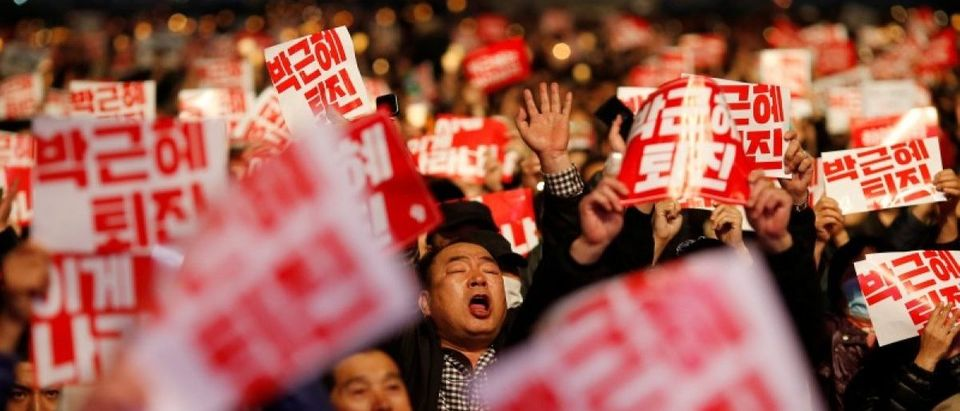 Tens of thousands of South Korean people chant slogans during a rally calling on embattled President Park Geun-hye to resign over a growing influence-peddling scandal in central Seoul