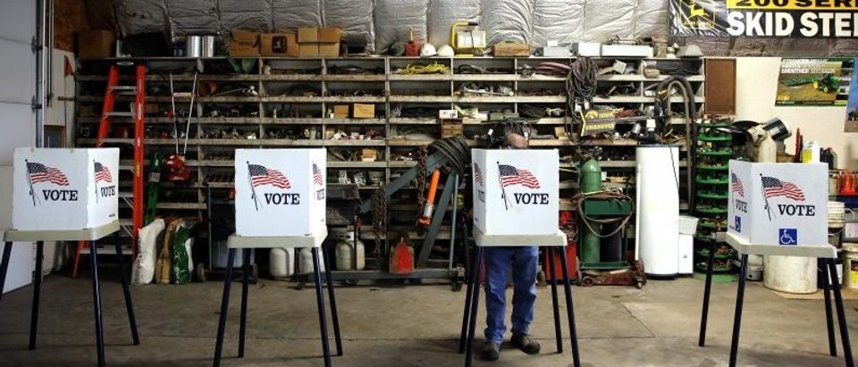 Voters cast their ballots at a polling station set up in a garage during the U.S. presidential election, near Fernald, Iowa