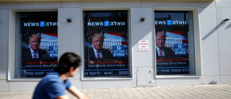 A man cycles past images of newly elected U.S. President Donald Trump which are displayed on monitors in Tel Aviv, Israel