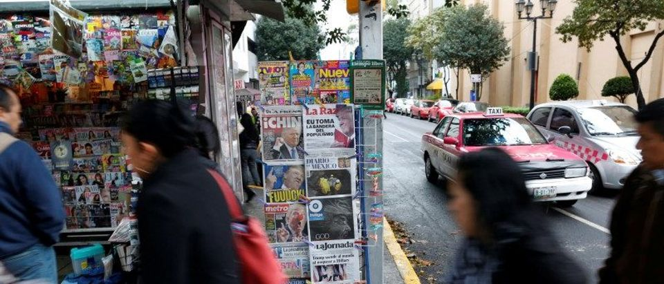 People walk past a newspaper stand in Mexico City
