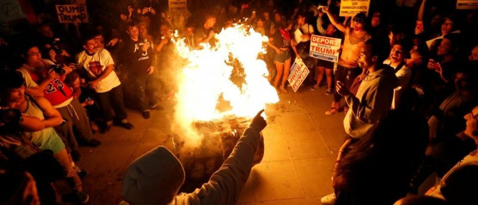 A Donald Trump pinata is burned by people protesting the election of Republican Donald Trump as the president of the United States in downtown Los Angeles, California U.S., November 9, 2016. REUTERS/Mario Anzuoni