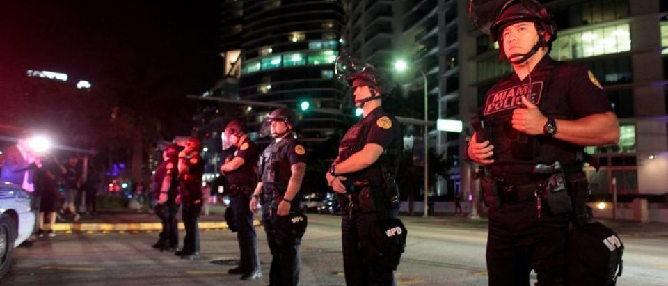 Police officers stand guard during a protest against U.S. President-elect Donald Trump in Miami, Florida, U.S. November 11, 2016. REUTERS/Javier Galeano