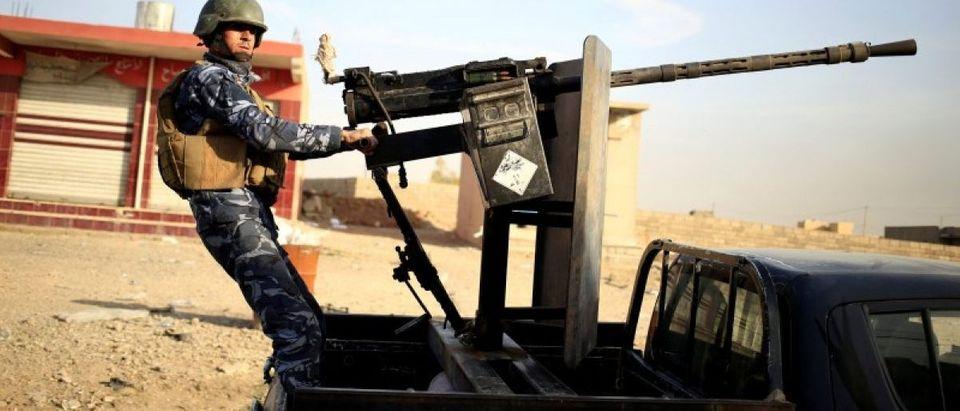 An Iraqi federal policeman aims his heavy machine gun on a vehicle in Samah district, eastern Mosul