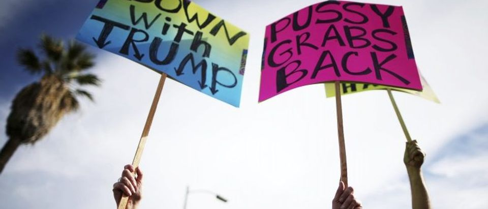 Protesters hold up signs during a march and rally against the election of Republican Donald Trump as President of the United States in Los Angeles