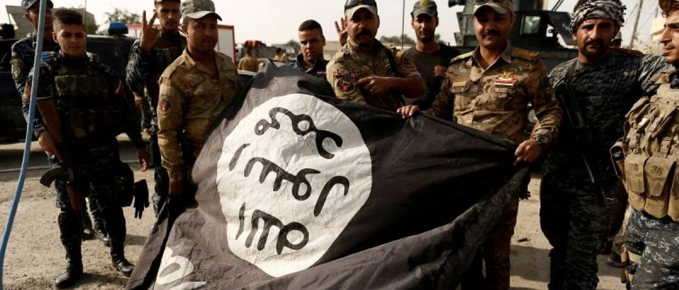 Iraqi soldiers pose with the Islamic State flag along a street of the town of al-Shura