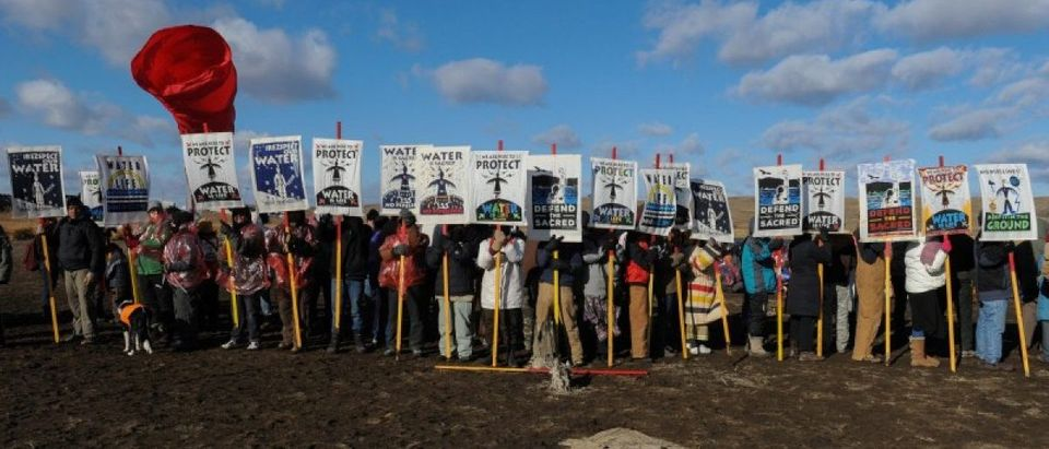 Protesters hold signs during a protest against plans to pass the Dakota Access pipeline near the Standing Rock Indian Reservation, near Cannon Ball, North Dakota, U.S.