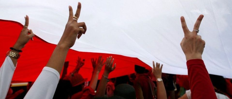 People gesture as they walk under a large Indonesian flag as they take part in a rally against what they see as growing racial and religious intolerance in the world's largest Muslim-majority country, in Jakarta, Indonesia November 19, 2016. REUTERS/Darren Whiteside