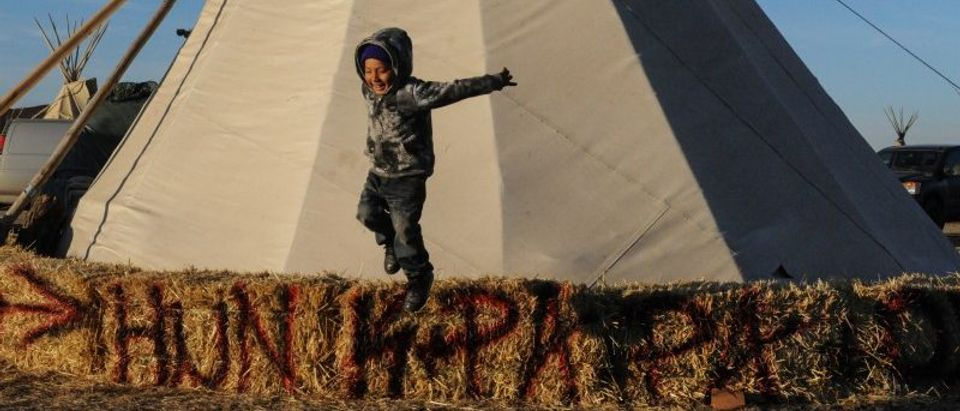 Kazlin Red Bear jumps from a hay bale in an encampment during a protest against plans to pass the Dakota Access pipeline near the Standing Rock Indian Reservation, near Cannon Ball, North Dakota