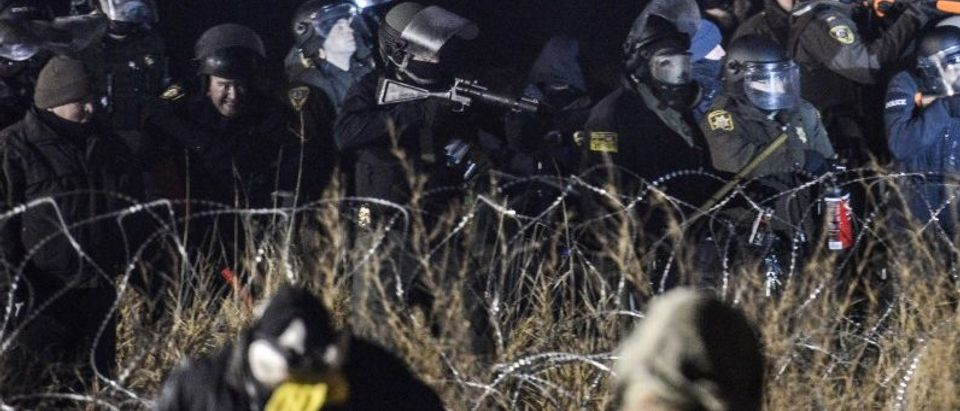 Police confront protesters with a rubber bullet gun during a protest against plans to pass the Dakota Access pipeline near the Standing Rock Indian Reservation, near Cannon Ball, North Dakota, U.S.