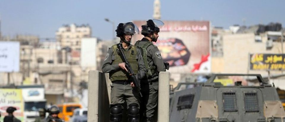 Israeli border policemen stand guard near the scene where Israeli police said a Palestinian was shot and killed by an Israeli security guard after the Palestinian tried to stab him, at Qalandiya checkpoint near the West Bank city of Ramallah