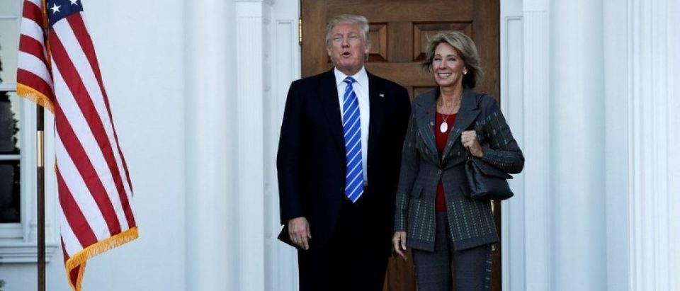 U.S. President-elect Donald Trump stands with Betsy DeVos after their meeting at the main clubhouse at Trump National Golf Club in Bedminster