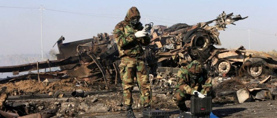 Chemical experts inspect the site of a suicide truck bomb attack, at a petrol station in the city of Hilla, south of Baghdad
