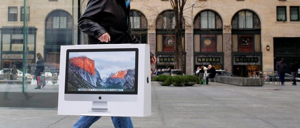 A man carries a newly purchased iMac from the Apple Fifth Avenue store during Black Friday sales in Manhattan, New York, U.S.