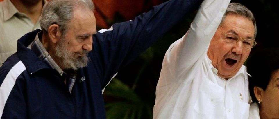 File photo of former Cuban leader Fidel Castro holding up the arm of his brother, Cuba's President Raul Castro, during the closing ceremony of the sixth Cuban Communist Party (PCC) congress in Havana