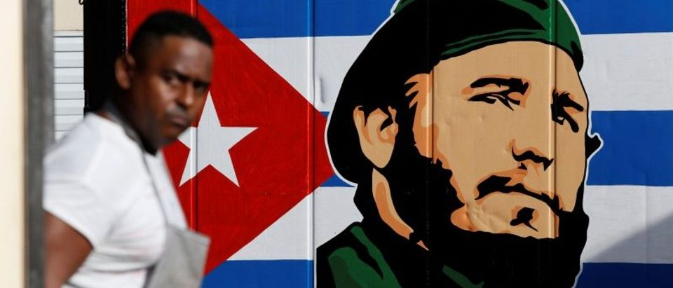 An employee of a state-owned candy store looks outside, near a painting depicting Cuba's former President Fidel Castro, following the announcement of Castro's death, in Havana
