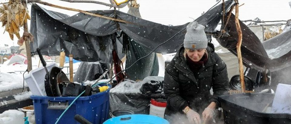 A woman washes dishes in the Oceti Sakowin camp in a snow storm during a protest against plans to pass the Dakota Access pipeline near the Standing Rock Indian Reservation, near Cannon Ball, North Dakota, U.S.