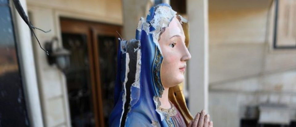 A damaged statue of the Virgin Mary is seen in a church in Qaraqosh