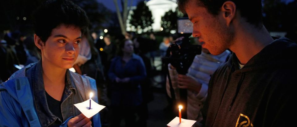 Anti-Trump demonstrators take part in a candlelight vigil in front of the White House in Washington