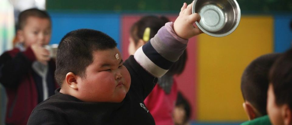 Lu Zhihao shows his empty rice bowl to his teacher during lunch time at a kindergarten in Foshan