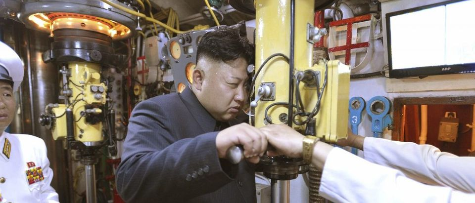 North Korean leader Kim Jong Un looks through a periscope of a submarine during his inspection of the KPA Naval Unit 167