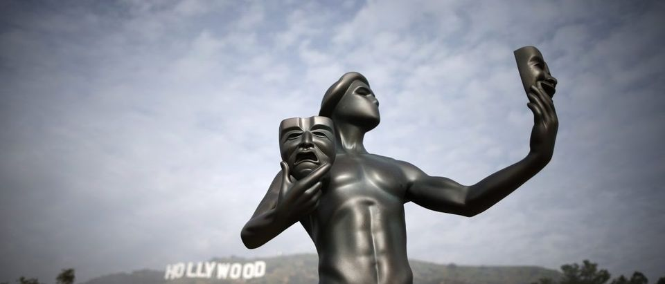 A Screen Actors Guild statue is seen in front of the Hollywood sign in Los Angeles