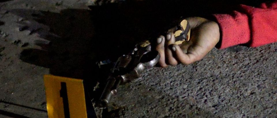 A revolver is seen in the hand of one of the three bodies of men lying on a street, who police said were gunned down in an armed encounter by policemen at a police checkpoint in Manila
