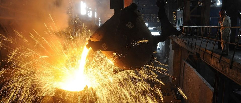An employee monitors molten iron being poured into a container at a steel plant in Hefei