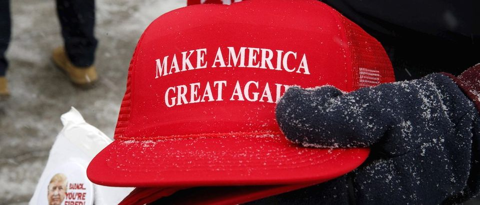"Trump campaign merchandise vendor holds Trump campaign ""Make America Great Again"" hats dusted with falling snow outside a Trump campaign town hall event in Londdonderry, New Hampshire"