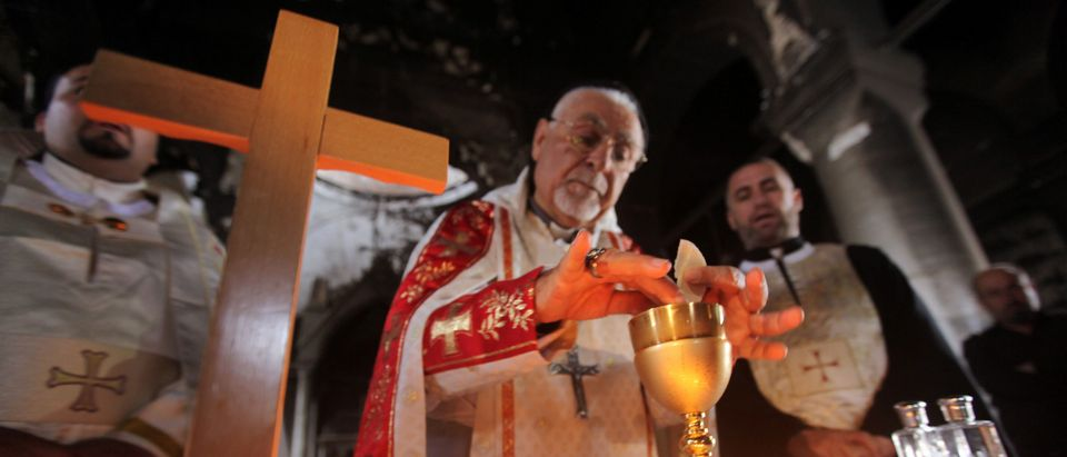 An Iraqi priest holds the first mass at the Grand Immaculate Church since it was recaptured from Islamic State in Qaraqosh